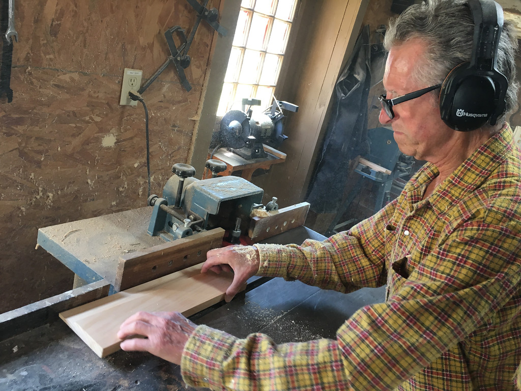 . Richard MacKay uses a shaper to form the contour on the raised panel of the cabinet door front he is crafting. Photo by Mary Leach
