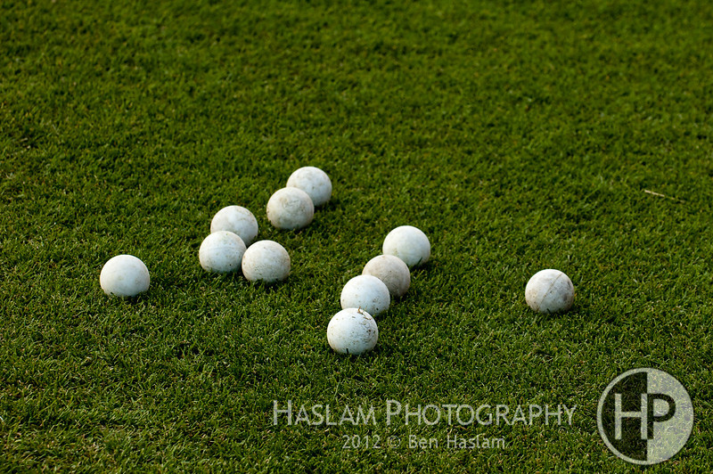 Many used lacrosse balls on green grass
