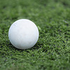 Single grey lacrosse ball on green grass