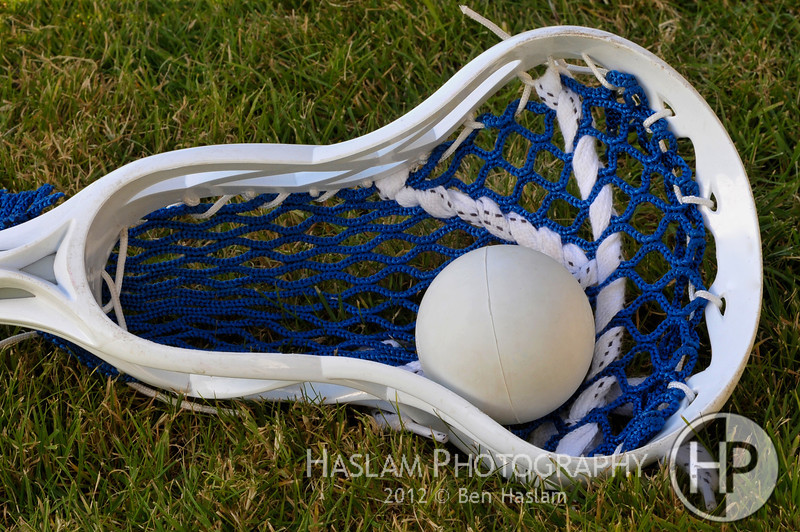 Lacross head with blue netting holding gray ball