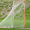 A single gray lacrosse ball going into an orange goal with white netting