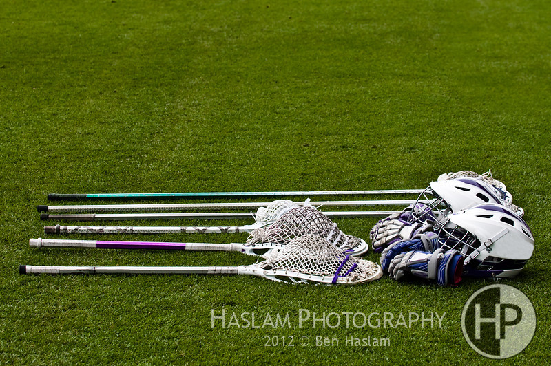 lacorsse sticks, helmets, gloves, goalie sticks on green grass