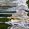 Many lacrosse sticks laying on the ground