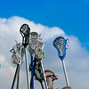Many lacrosse sticks and heads held high in sky