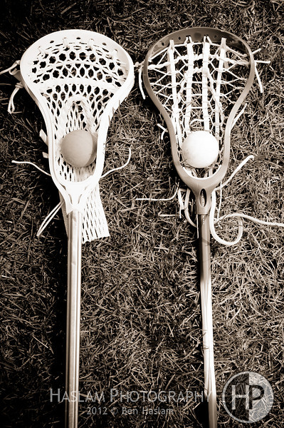 Two lacrosse heads and sticks with ball on grass - black and white