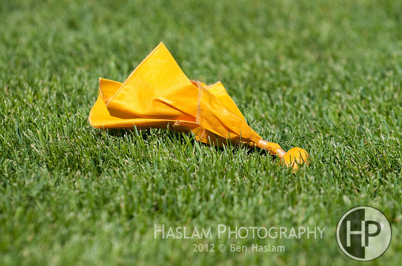 Yellow Penalty Flag on Green Grass During Play