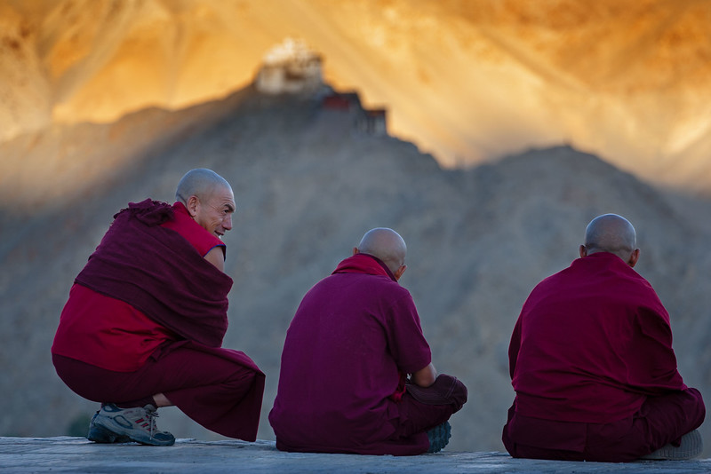 Three monks at Shanti Stupa at sunset.