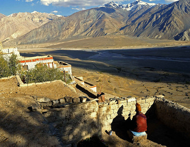 A monk prays on the roof top of Karsha monastery