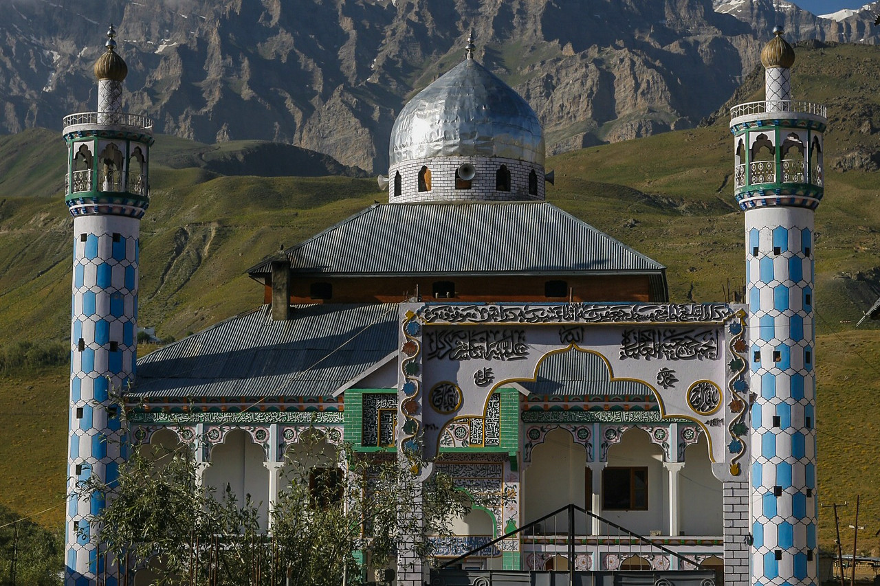 A mosque in Dras with its colourful columns and decorative inscriptions adds colour to the other brown landscape surrounded by the Greater Himalayas.