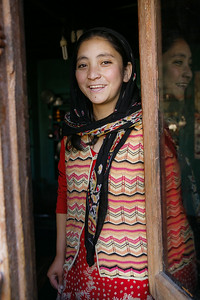 Young girl from Drass, wearing a bright red salwar kameez and a sweater, head covered, stands by the window in her house and smiles for the camera as she casts her reflection in the window glass.