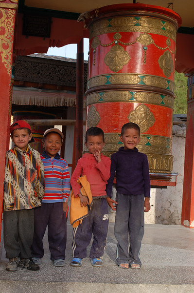 Deskit: Young villagers pose in front of one of the town's many prayer wheels