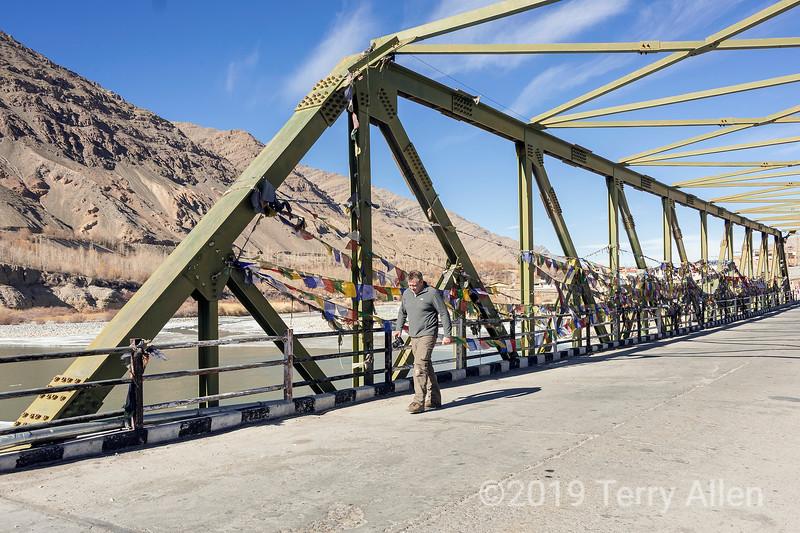 Man walking across the Upshi Bridge across the Indus River, festooned with prayer flags, Keylong-Leh Road, Ladakh, India