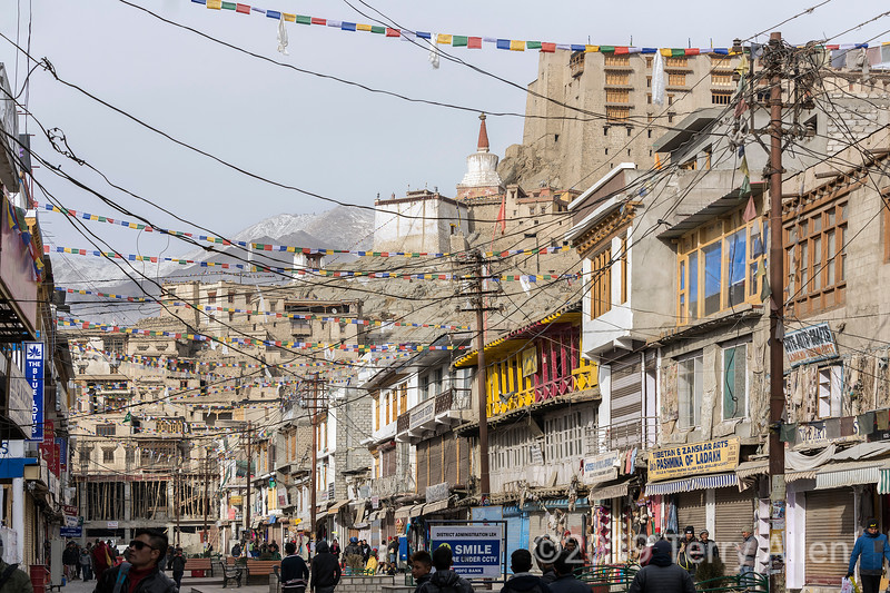 Bazaar Road with prayer flags and electric wires, looking towards Leh Palace, Ladakh, India