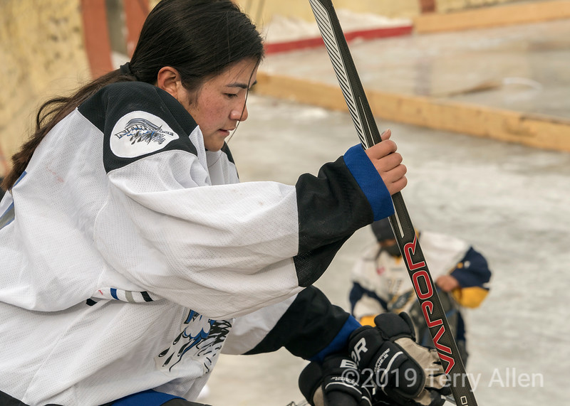 Woman hockey player getting ready for a game, outdoor ice rink, Leh, Ladakh