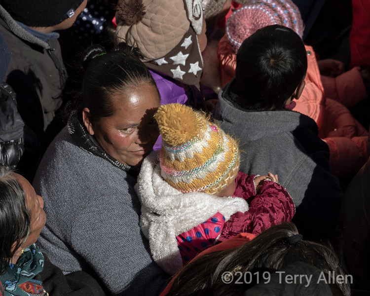 Woman and baby in a shaft of light, Gustor festival, Spituk Gompa, Leh, Ladakh