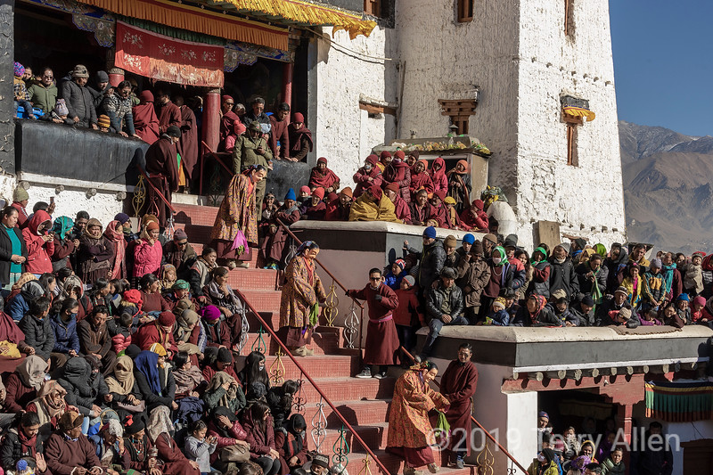 Masked Cham dancers enter the courtyard for the Gustor festival, Spituk Gompa, Leh, Ladakh. The mask dance, Cham is the highlight of Spituk Gustor. Considered as an act of cleansing of evil forces, Cham Dance is an elaborate masked and costumed dance.<br /> Ladakh tops the list of the best places to see Cham Dance in India. The region known as 'Mini Tibet' has ancient roots in Buddhism. <br /> The dance is more like a drama representative with characters that represent the guardian divinities (Dharmapalas) of the Buddhist pantheon, and the patron divinities of the Geluk-pa order. Monks dress up in beautiful masks made of clay and paper painted with natural colors and polished with gold and silver while the dress is usually silk and brocade. The dance is accompanied by music played on long horns, cymbals, conch shells, bells and many other instruments.