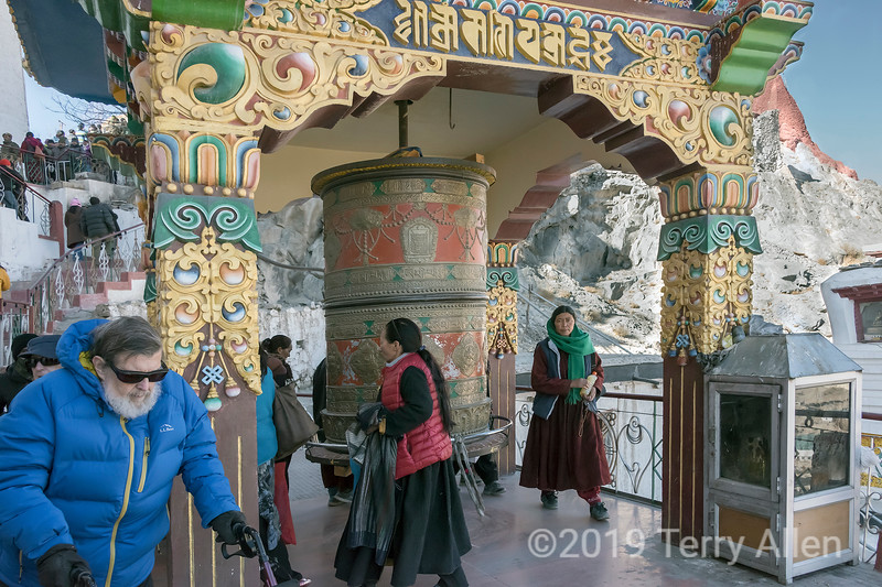 Festival goers turn a large prayer wheel, Spituk Gompa, Leh district, Ladakh