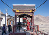 Buddhist monk turning the giant prayer wheel, Spituk Gompa, Leh district, Ladakh