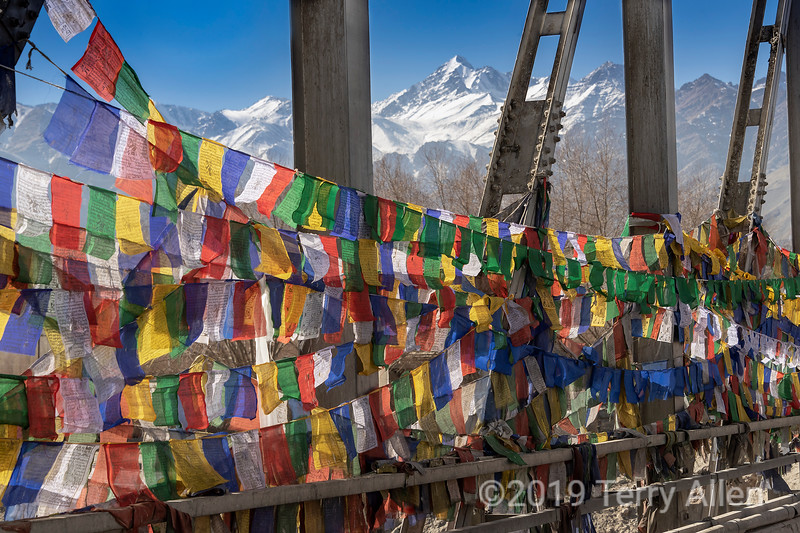 Prayer flags on the Chuckhot Rd bridge looking towards the Ladakh Range, Leh, Ladakh