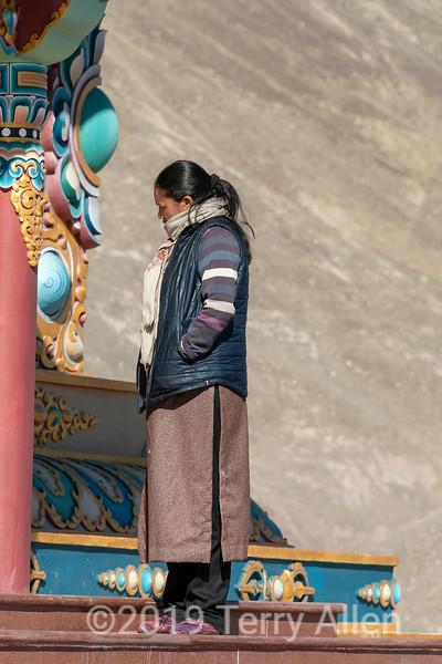 Ladakh woman in traditional attire studies the decorations on the Stok Buddha, Stok, Ladakh