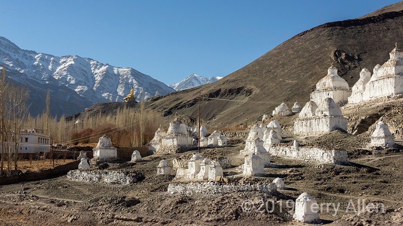 Old stupas below Stok Palace with giant statue of Gautama Buddha in background, Stok, Ladakh
