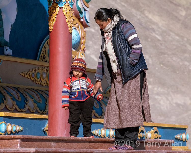 Woman guiding her young son down the steps of the Stok Buddha, Stok, Ladakh