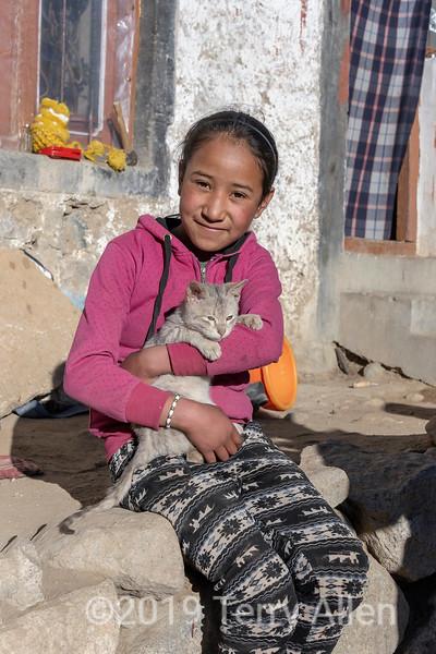 Ladakh girl with pet cat sitting on her door stoop, Ulley, Ladakh