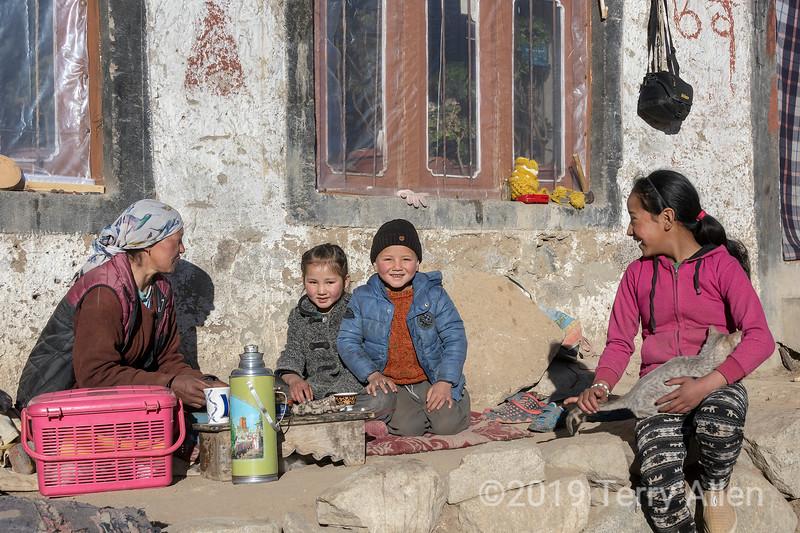 Ladakh family sitting in the winter sun, Ulley, Ladakh