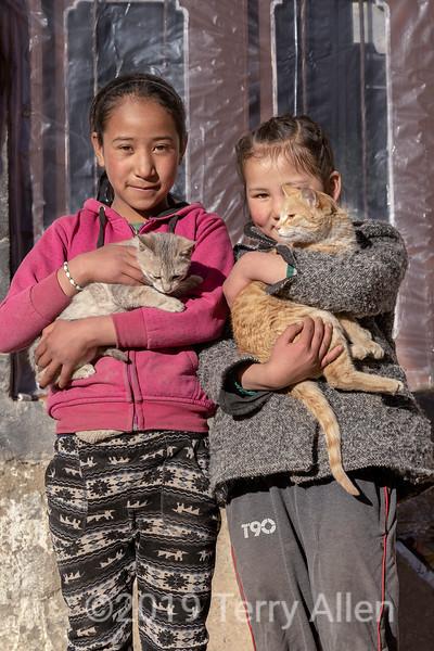 Two Ladakh girls cuddling their pet cats, Ulley, Ladakh
