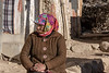 Ladakh woman sitting in frot of her house on a cold day, Ulley, Ladakh
