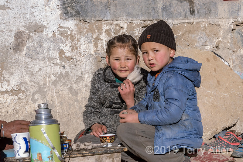 Portrait of a boy and girl sitting on their front stoop, Ulley, Ladakh