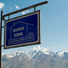 Sign in Karsha Village with a view of the Great Himalayan Range