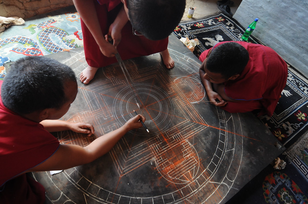 Monks starting a sand mandala.  The most important/difficult part is actually the chalk lines that are put on the board before the sand is applied.