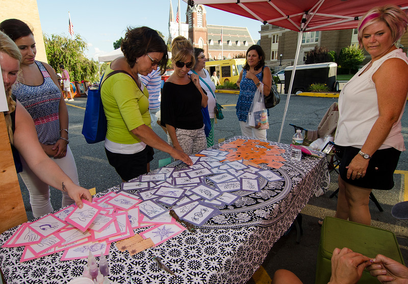 Women check out the henna tattoo table during Ladies Night Out in Leominster on Thursday evening. SENTINEL & ENTERPRISE / Ashley Green