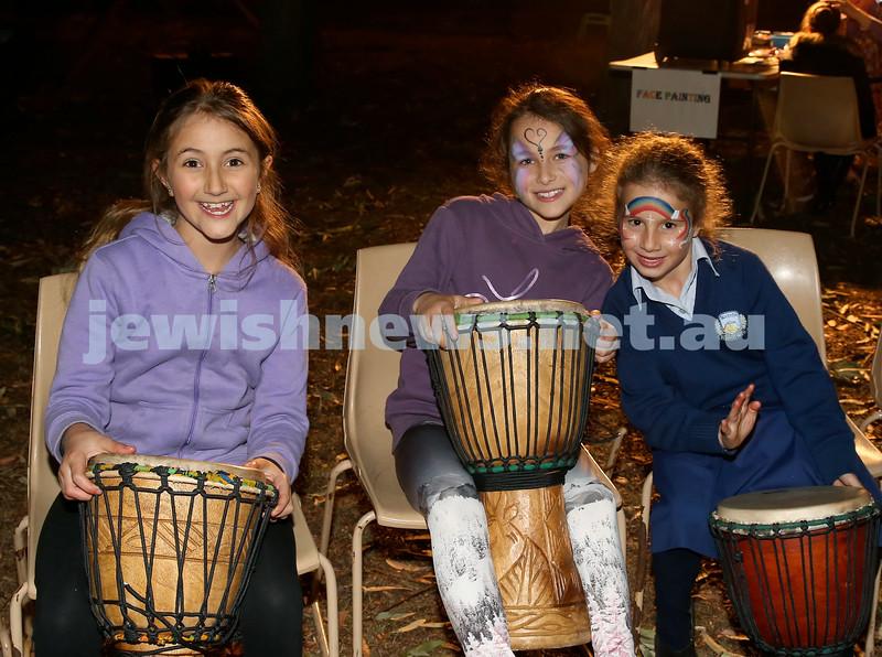 Lag B'Omer at Chabad North Shore. (from left) Sahara Ezra, Erin Kruger, Ariella Cohen drumming around the bonfire. Pic Noel Kessel.