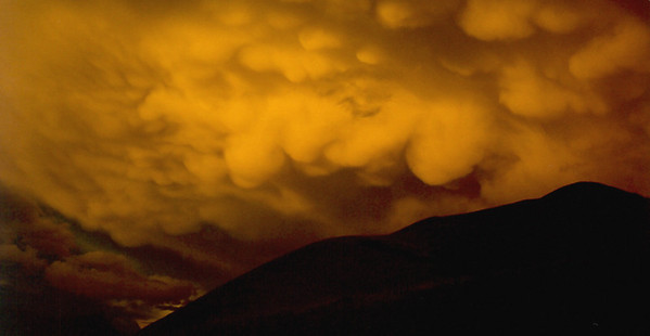 Some mammatus clouds catch waning evening light as a thunderstorm moves east; Michigan Lakes, Never Summer Mountains, Colorado.