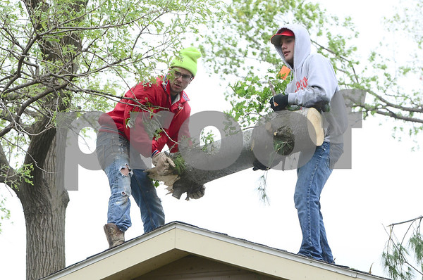 -Messenger photo by Jesse Major<br /> <br /> South Central Calhoun senior Dylan Addison and junior Kyle King throw a log down from a house in the path of the tornado Sunday in Lake City.