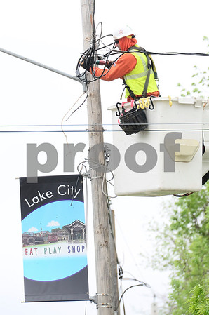 -Messenger photo by Jesse Major<br /> <br /> Crew members worked to restore power in Lake City following the tornado Sunday. Officials expected power to return by the end of Monday.