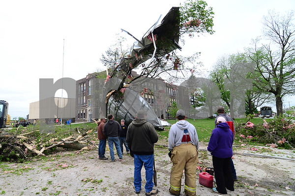 -Messenger photo by Jesse Major<br /> <br /> Volunteers look at the roof of South Central Calhoun High School, which blew off when the tornado Sunday passed over. When the tornado tore the roof off, there were at least 100 people inside for an awards ceremony.