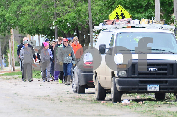 -Messenger photo by Jesse Major<br /> <br /> About a dozen volunteers walk along a street in Lake City as they help clear debris from homes.