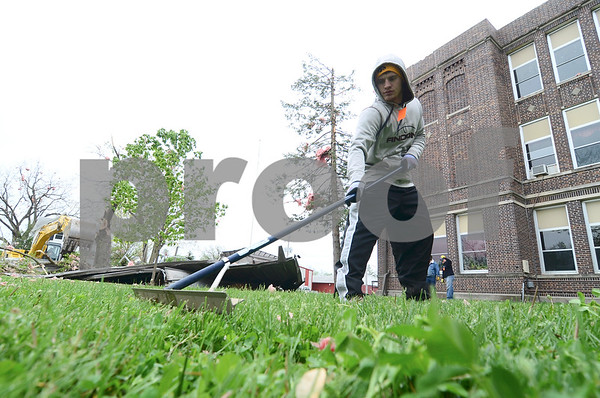 -Messenger photo by Jesse Major<br /> <br /> John Curran, a senior at South Central Calhoun High School, rakes up leaves, twigs, insulation and other debris from in front of the high school.