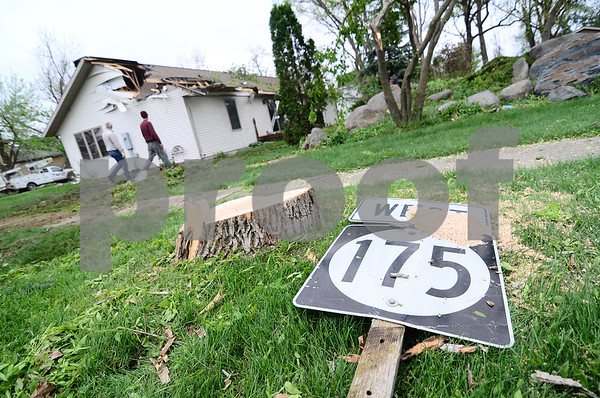 -Messenger photo by Jesse Major<br /> <br /> A sign for Iowa Highway 175 sits on the ground in front of homes that were in the path of the Lake City tornado Sunday.