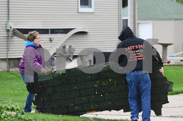 -Messenger photo by Jesse Major<br /> <br /> Trish Dick and her fiance Mike Christensen move a section of their roof that blew off as Sunday's tornado tore past their house in Lake City.