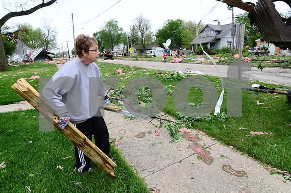-Messenger photo by Jesse Major<br /> <br /> Becky Remsburg works to remove debris from her yard after Sunday's tornado in Lake City.