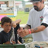 Kristi Garabrandt - The News-Herald <br /> Jaiden Avila, 7, Phoenix, AZ throws back a fish he caught after Beau Allen of First Bite Fish Tanks explains to him how it's done.