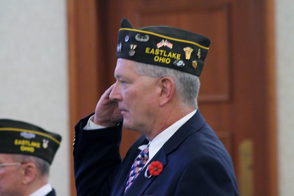 . Kristi Garabrandt � The News-Herald <br> Willowick-Eastlake VFW Post Commander Robert Webber Salutes the flag during the signing of the National Anthem during Eastlake\'s Veterans Day Ceremony.