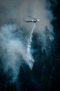 A Department of Natural Resources helicopter drops water as a wildland fire burns along East Beach Road on the northern shore of Olympic National Park's Lake Crescent on July 29, 2020. (Jesse Major)