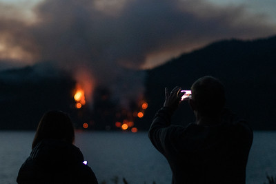 A man takes a picture as a wildland fire burns along East Beach Road on the northern shore of Olympic National Park's Lake Crescent on July 29, 2020. (Jesse Major)