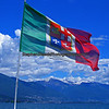 Ferry boat flag framing a portion of the Swiss Alps seen in the background on Lake Maggiore.