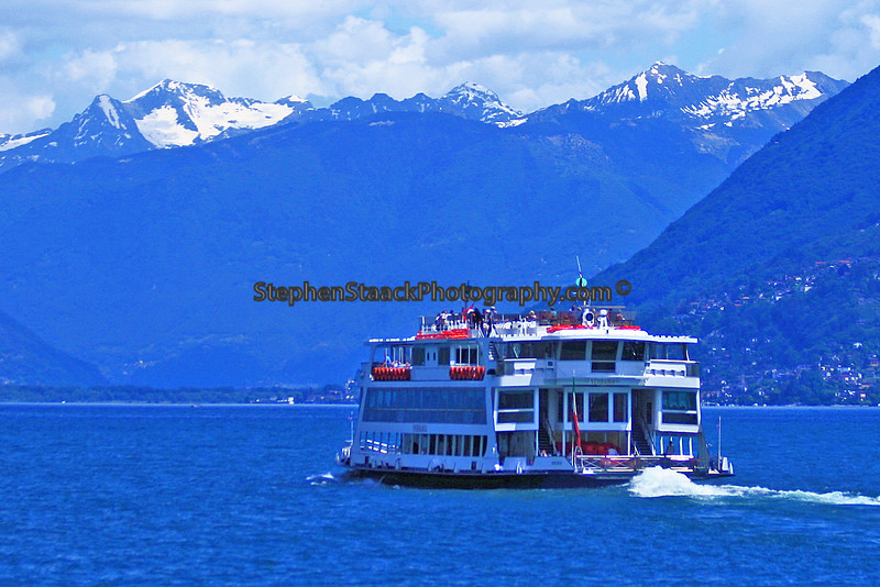 Ferry boat heading towards various towns on Lake Maggiore with the with the Swiss Alps in the background.